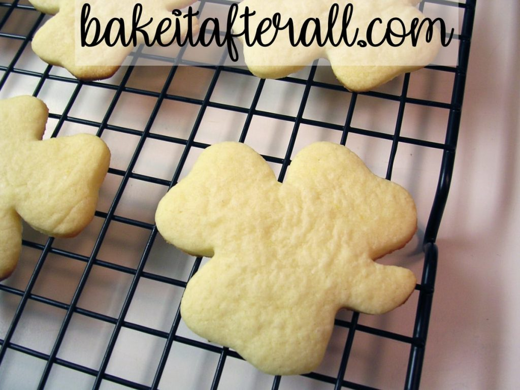 baked shamrock shaped sugar cookies on a cooling rack