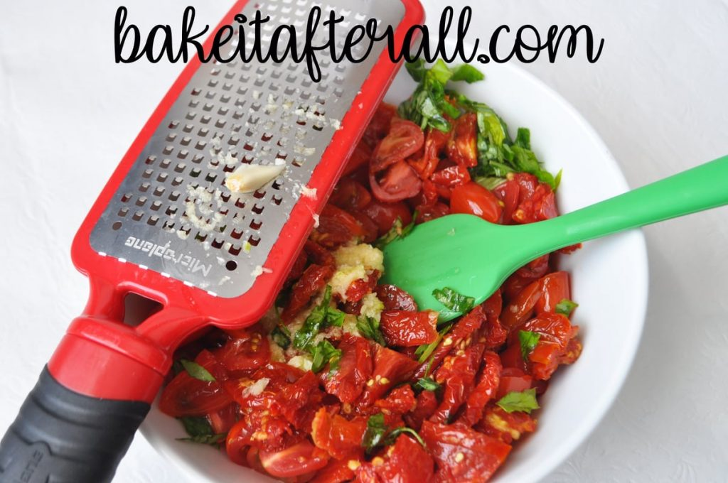 garlic on a microplane grater over the bowl of tomato mixture