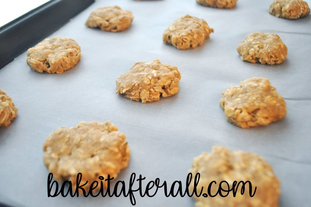 flattened balls of dough on a parchment lined cookie sheet