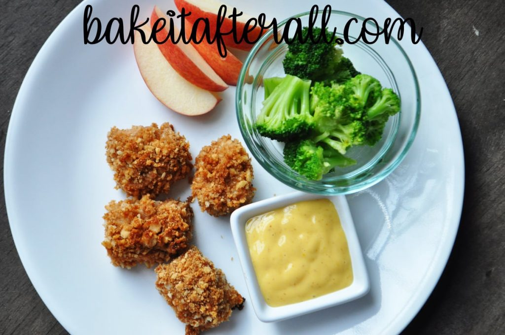 oven fried honey chicken nuggets on a plate with apple slices and broccoli