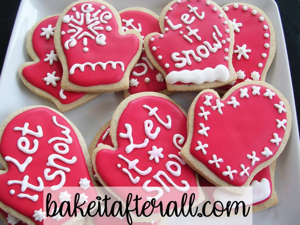 "Brown Sugar and Spice cookies with royal icing decorated with the words ""let It Snow"" on a white plate"