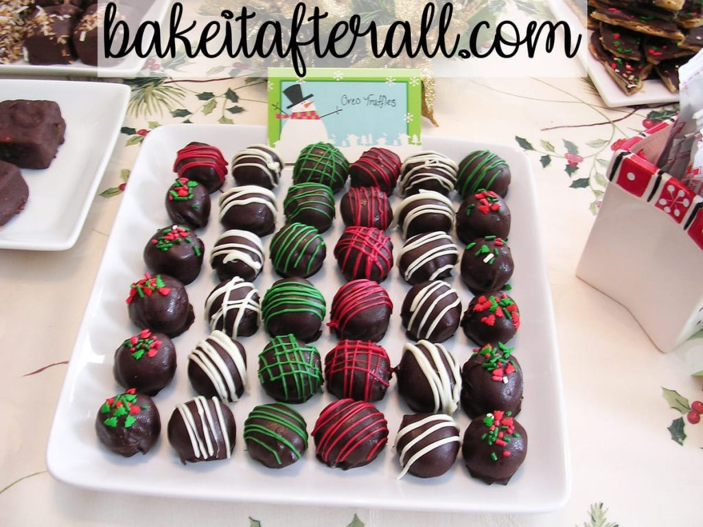 holiday oreo truffles on a platter on a holiday dessert table decorated with striped of red and green and Christmas sprinkles for a Holiday Open House