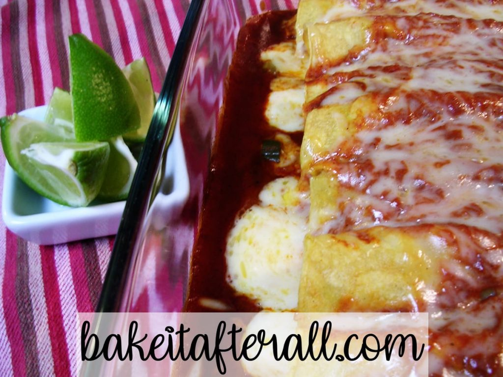 Chicken Enchiladas with Red Chile Sauce with limes in a dish