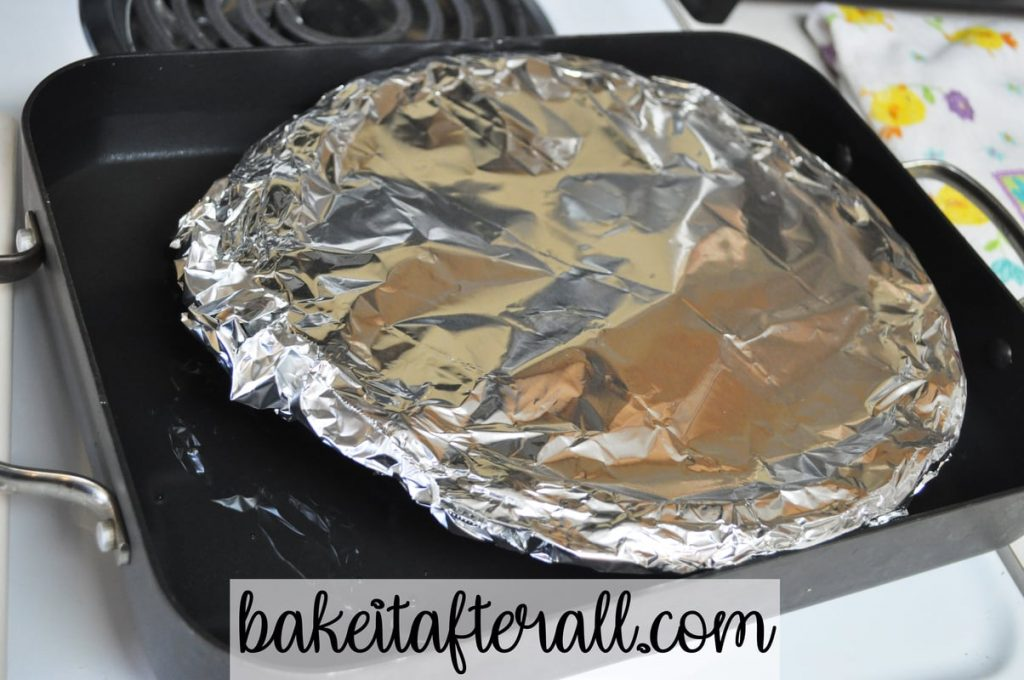 roasting pan with foil covered pie plate inside