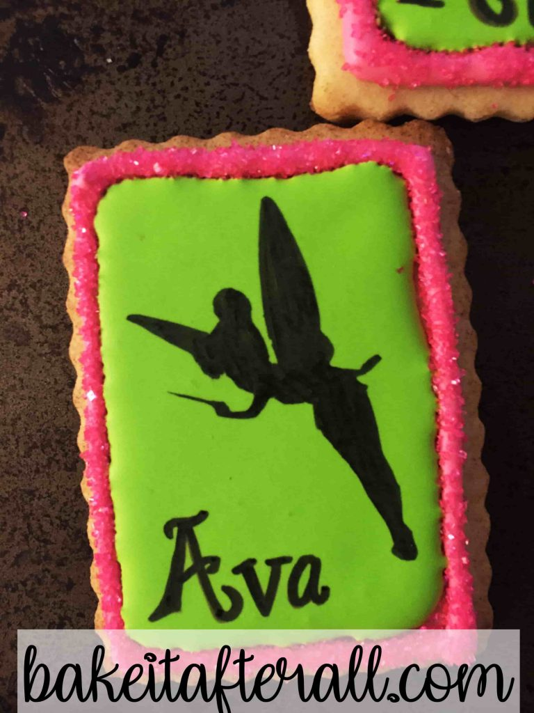 up close of a royal icing cookie with a Tinkerbell silhouette on top