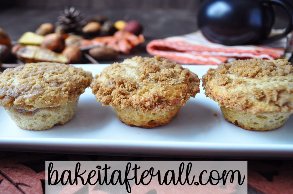 allspice crumb muffins on a white plate with fall decor behind