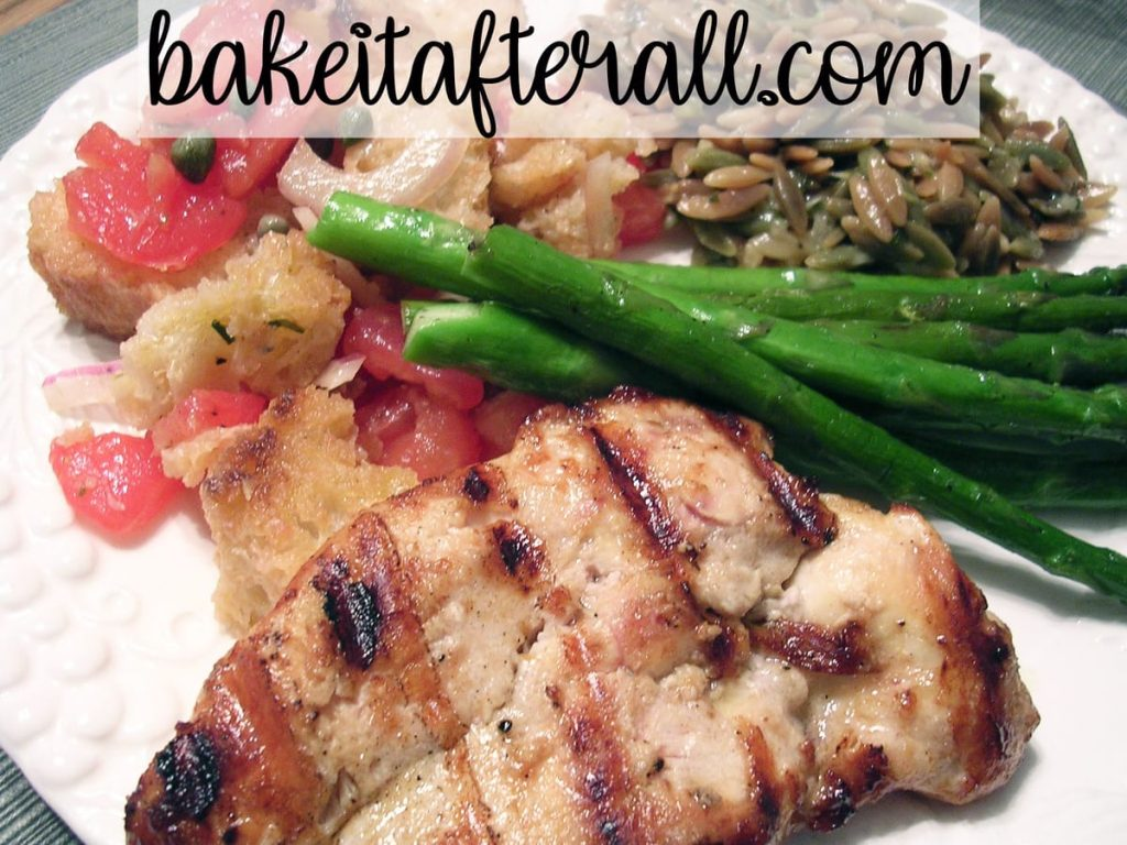 panzanella tomato bread salad on a plate with parmesan basil orzo, Italian dressing marinated chicken breast, and grilled asparagus