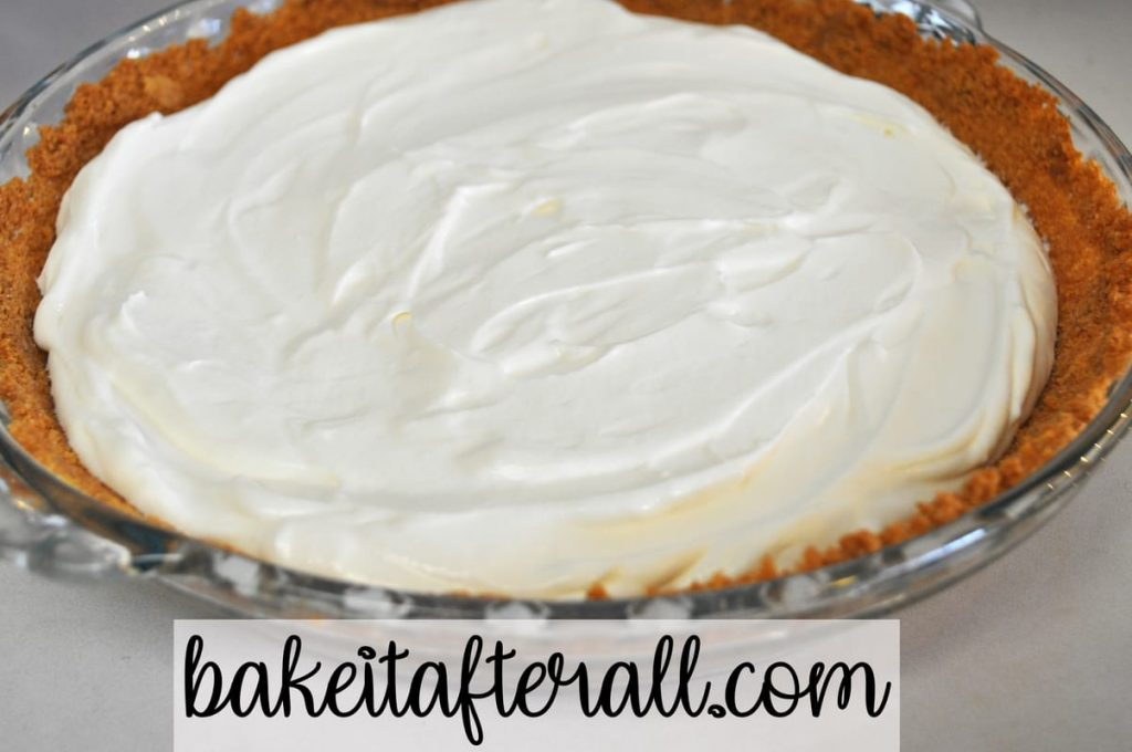 cheesecake filling inside graham cracker crust in glass pie plate on table