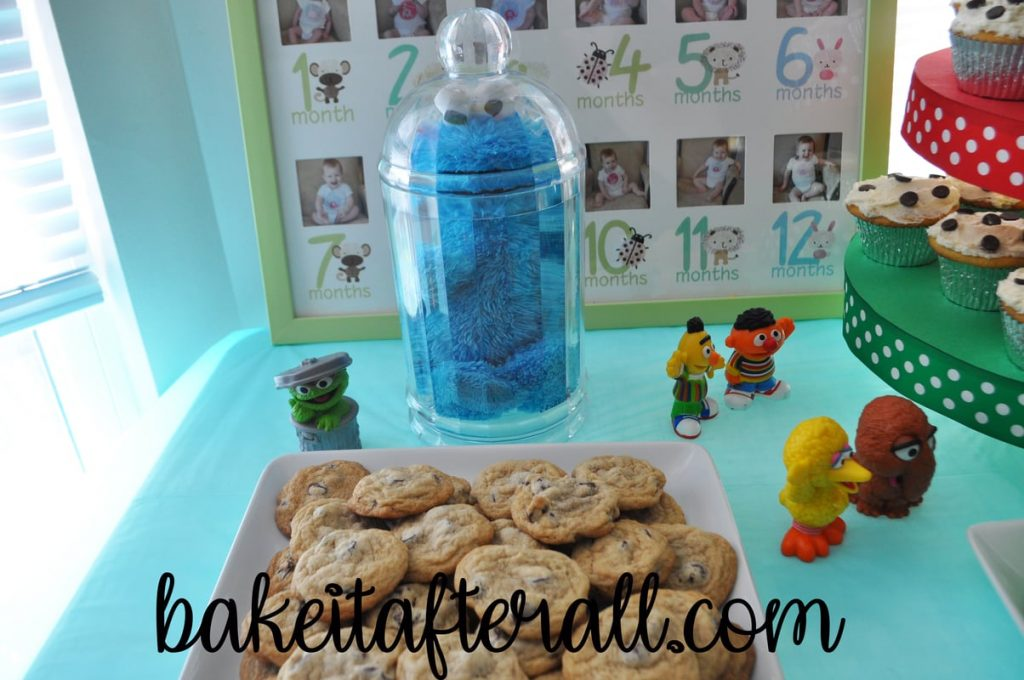 Cookie Monster trapped in jar behind plate of chocolate chip cookies