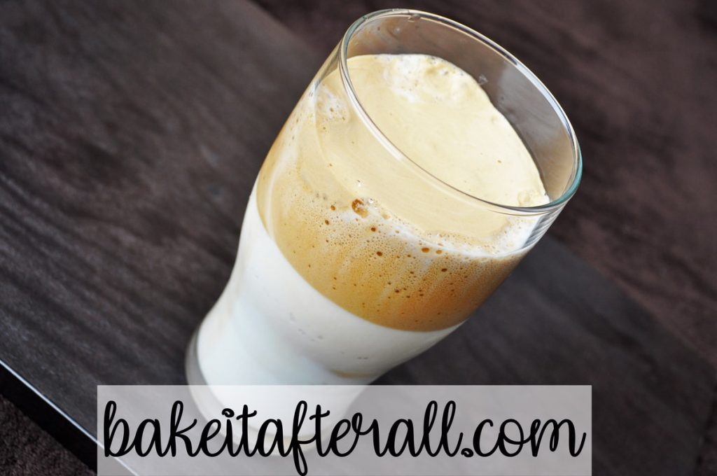 whipped coffee on top of milk in a glass