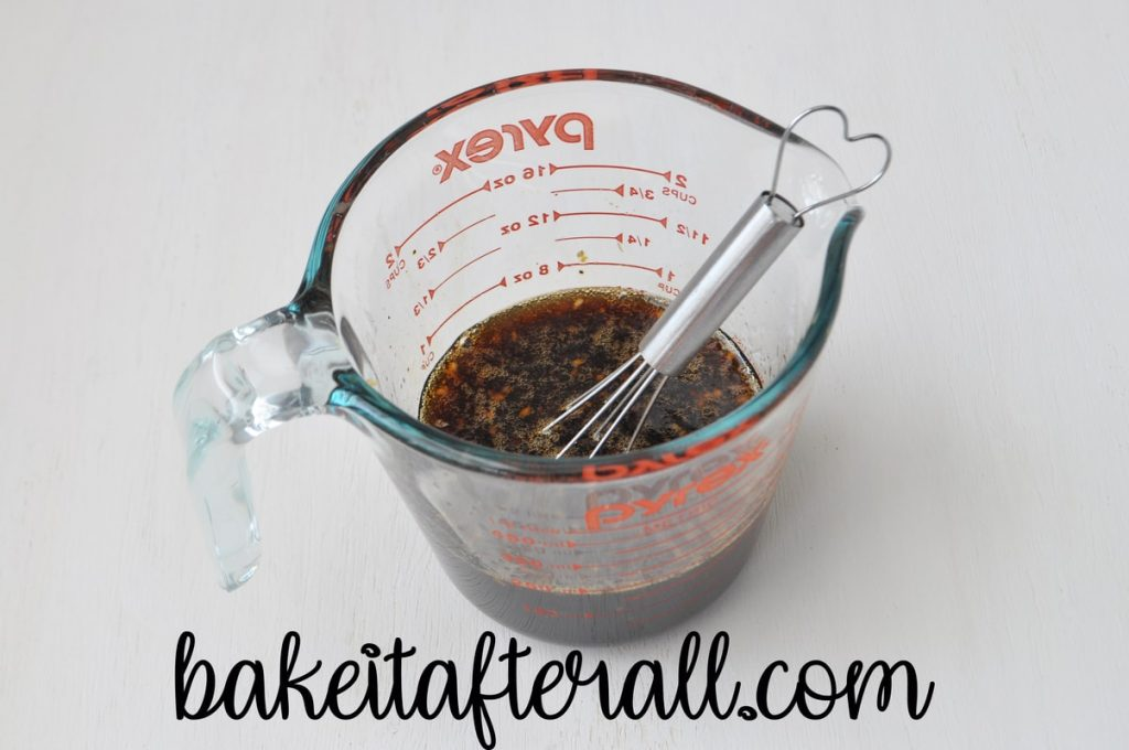 glass measuring cup filled with honey garlic marinade ingredients with a small wire whisk inside