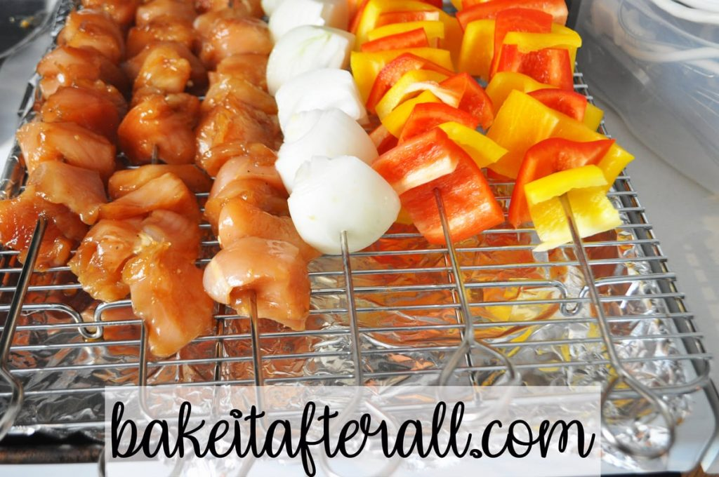 baking rack with chicken, onion, and pepper skewers on top