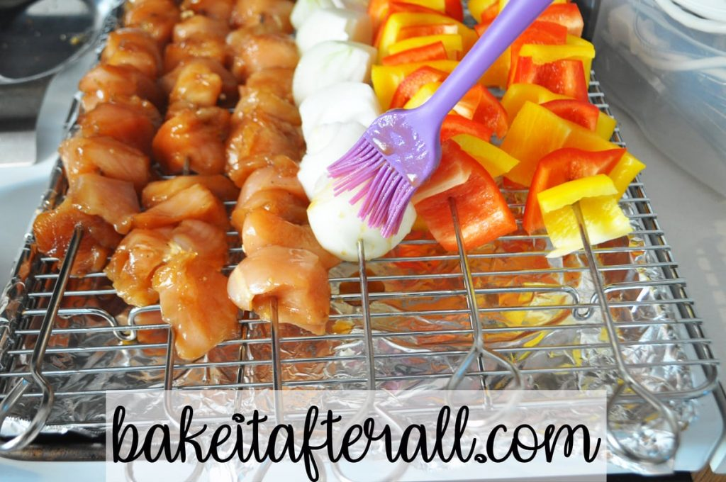 silicone pastry brush brushing marinade on onion skewer next to honey chicken kabobs