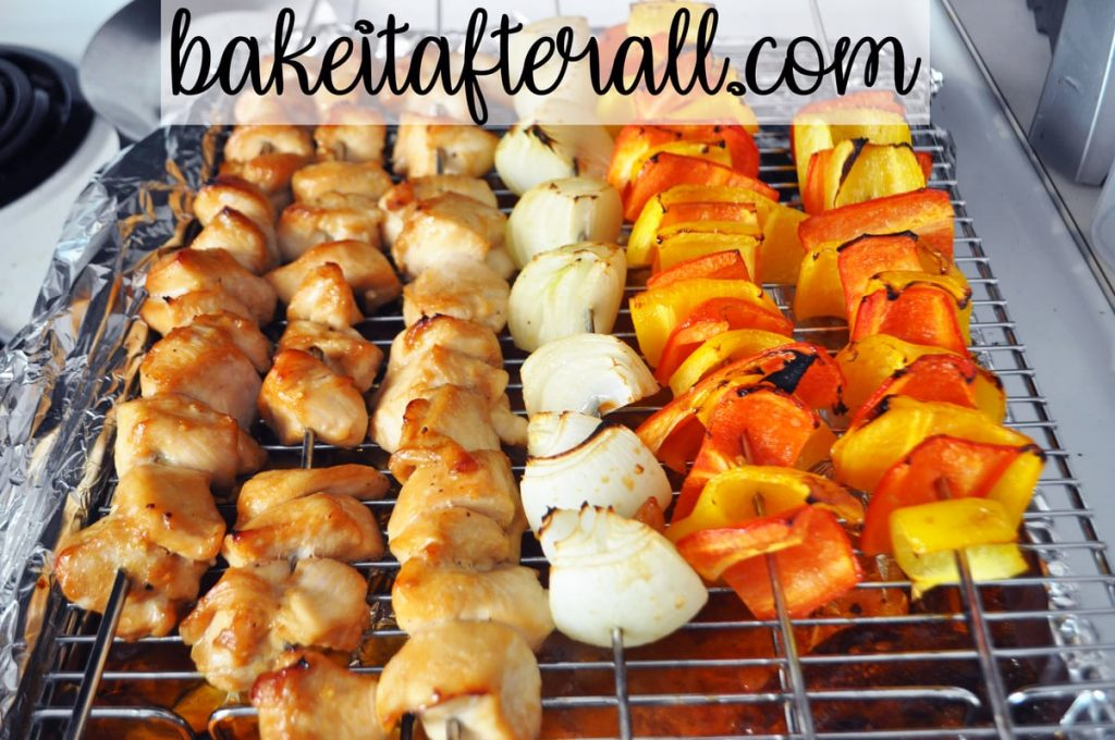 cooked honey chicken kabobs, onion, and bell pepper kabobs on a baking rack