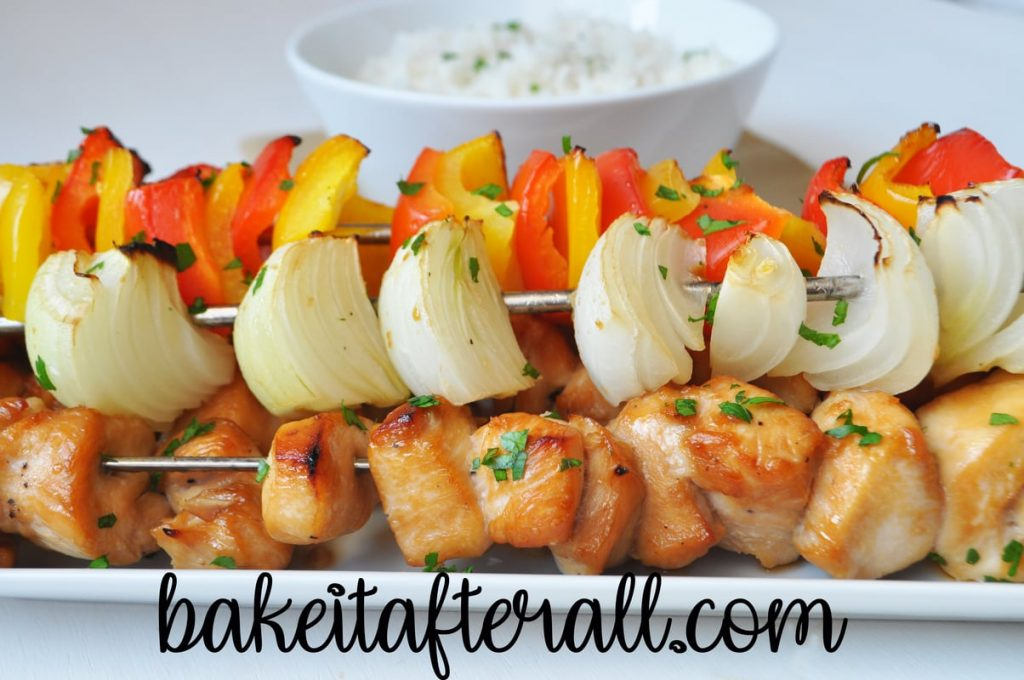 Honey Chicken Kabobs on a platter with a bowl of rice behind it