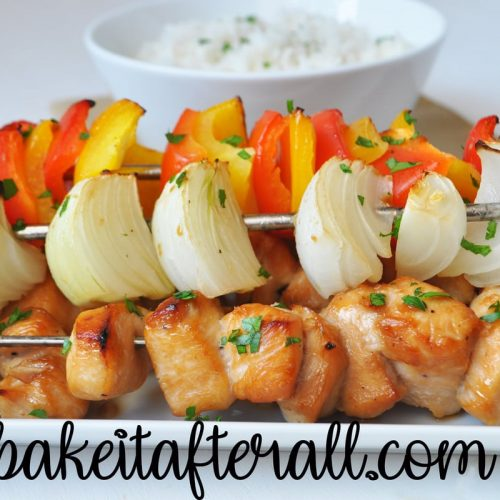 honey chicken kabobs on a plate with rice in a bowl behind it