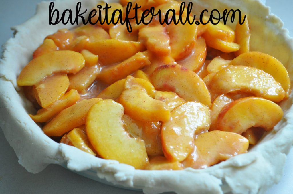 fresh peaches poured into a pie plate lined with gluten free pie crust dough