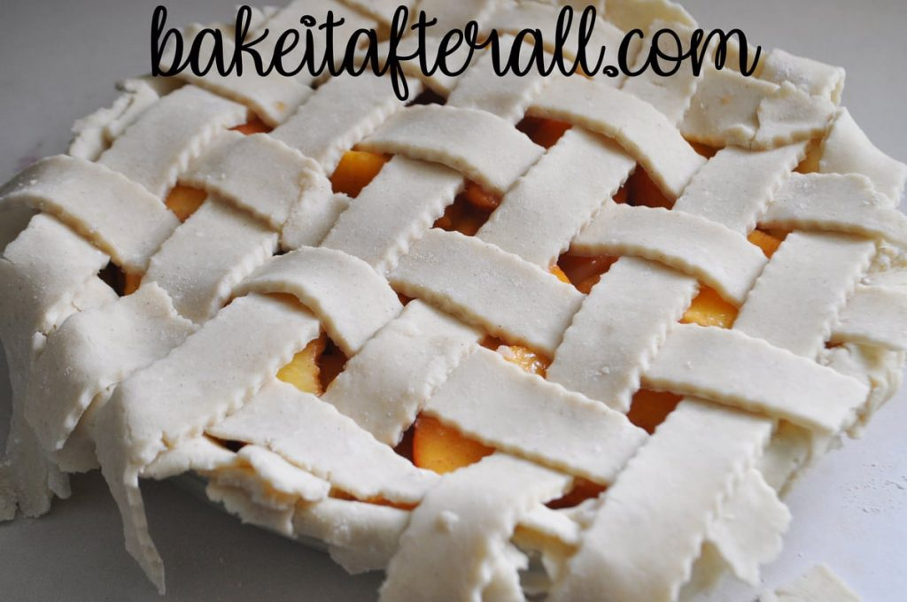 strips of gluten free pie dough arranged in lattice on top of fresh peach pie