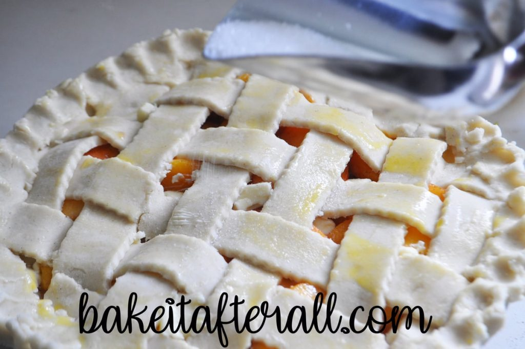 sugar being sprinkled on top of lattice topped pie crust brushed with egg wash