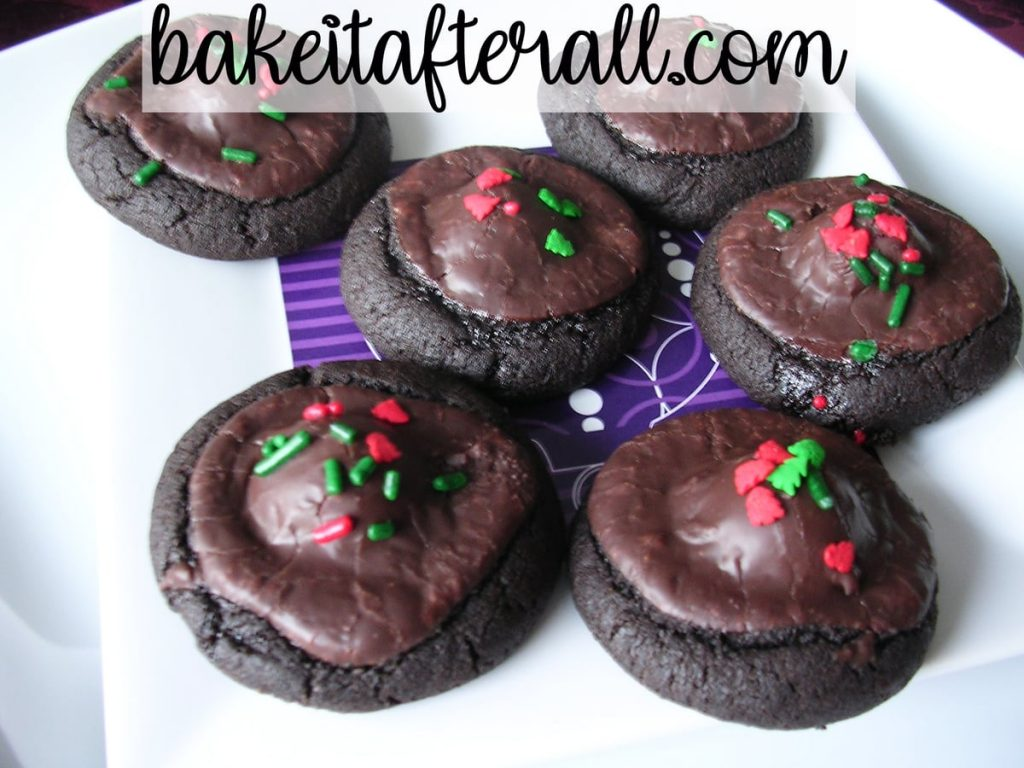 dark chocolate covered cherry cookies decorated with Christmas sprinkles on a white plate