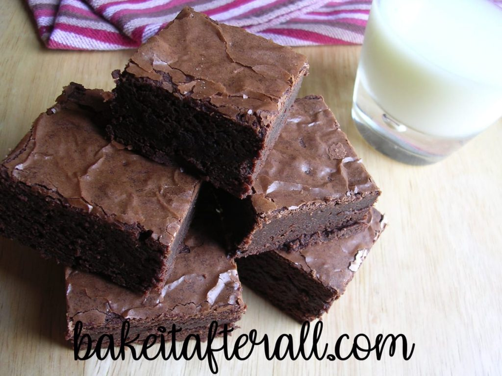 Chewy Fudgy Brownies on a wooden table with a glass of milk
