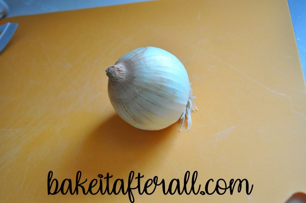 intact onion on a cutting board