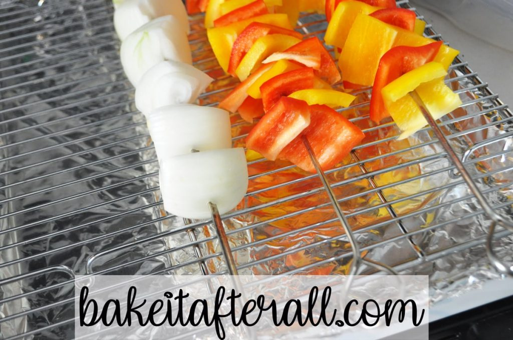 baking rack with onion and pepper skewers on top