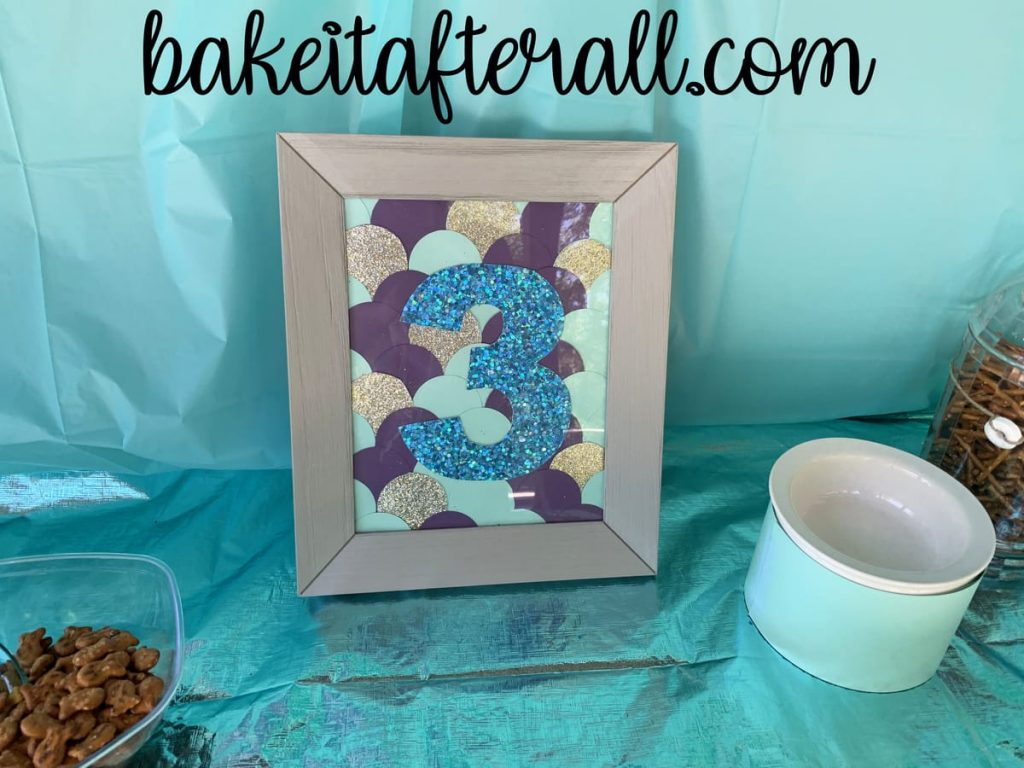 mermaid scales made with cardstock with a 3 on top inside a picture frame