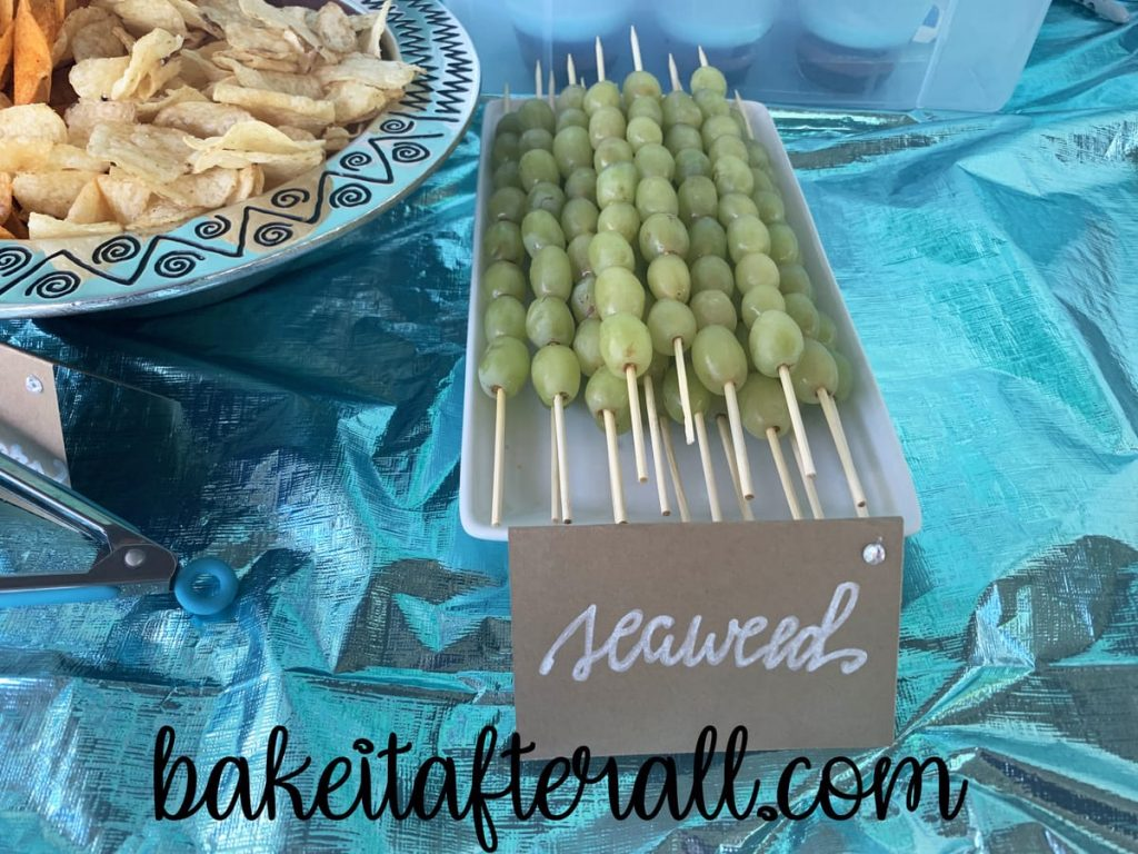 "green grapes on wooden skewers labeled ""seaweed"""
