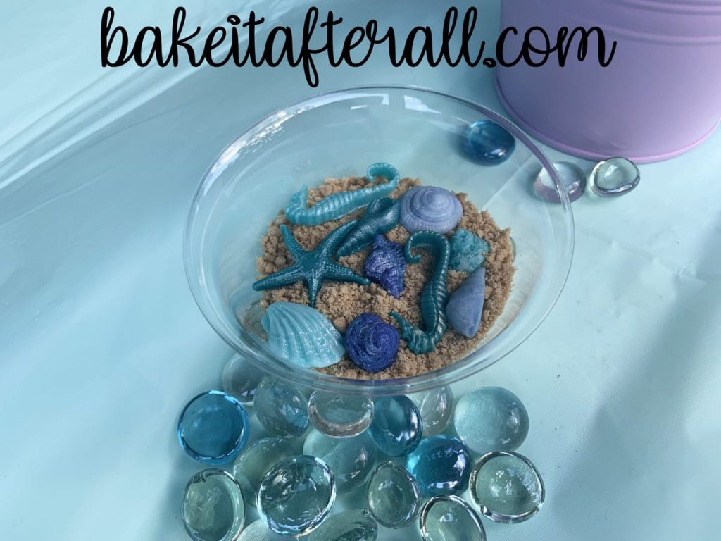 bowl with fondant shells and seahorses in crushed graham crackers to look like sand