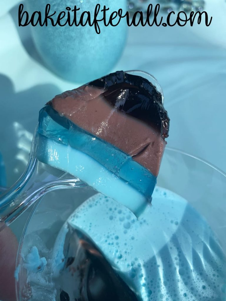 4 layers of jello on a plastic spoon