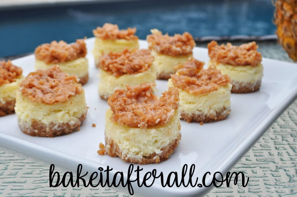 mini pina colada cheesecakes topped with candied coconut topping on a white plate