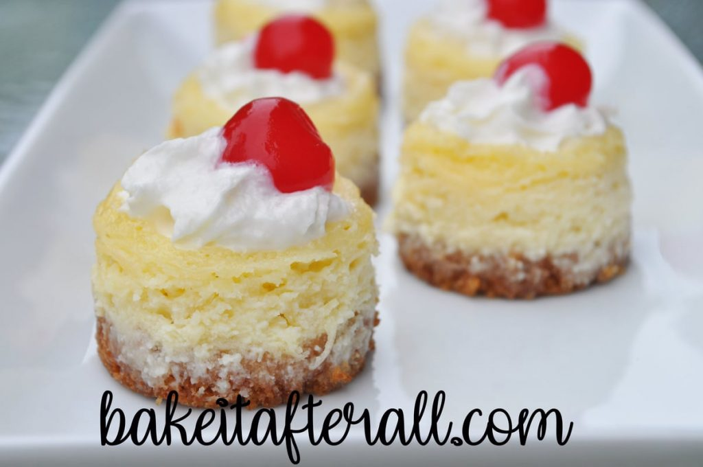 mini pina colada cheesecakes topped with whipped cream and maraschino cherry on a white plate