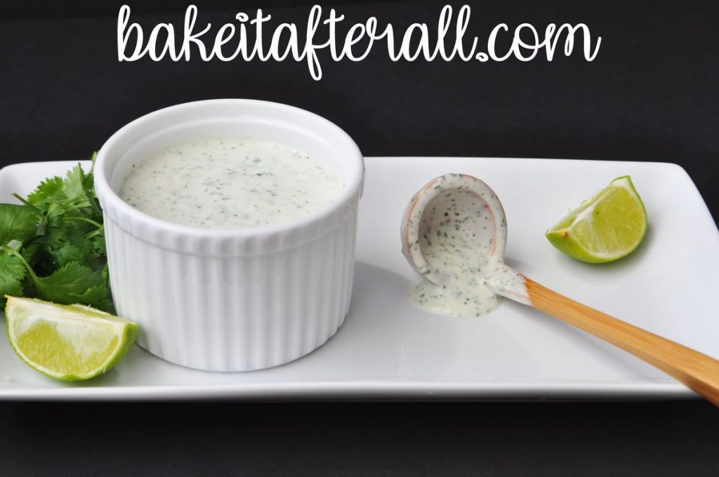 Cilantro Lime Crema Costco Copycat in a white ramekin on a plate with a wooden spoon next to it