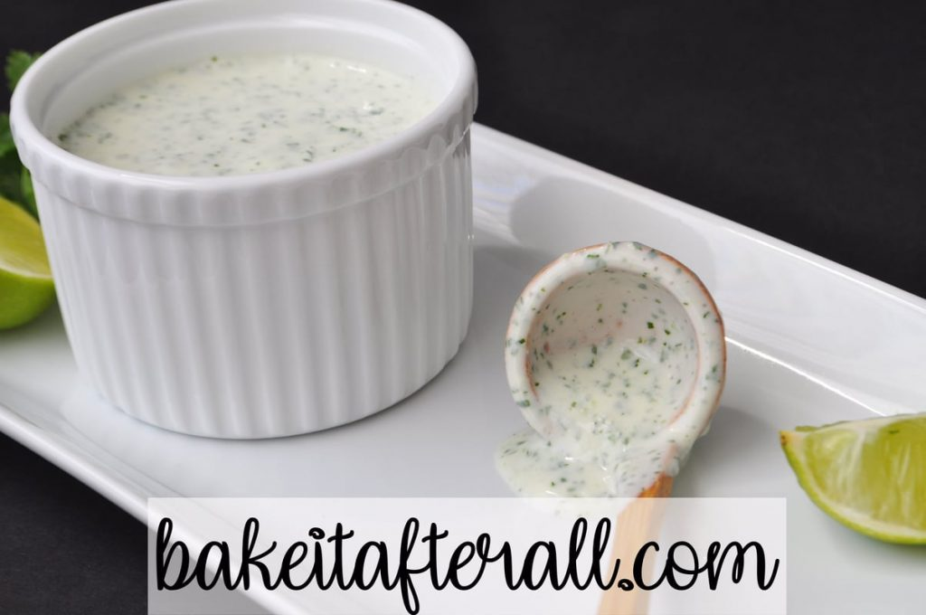 a white ramekin filled with Cilantro Lime Crema Costco Copycat on a plate