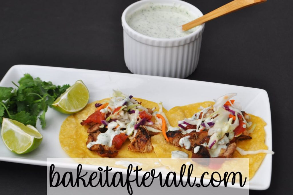 Cilantro Lime Crema Costco Copycat on top of Costco Chicken Street Tacos on a plate with limes and cilantro garnish