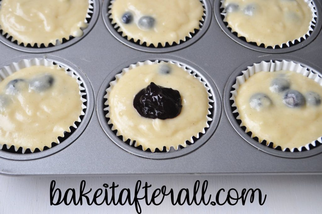 muffin batter with a scoop of homemade blueberry jam on top