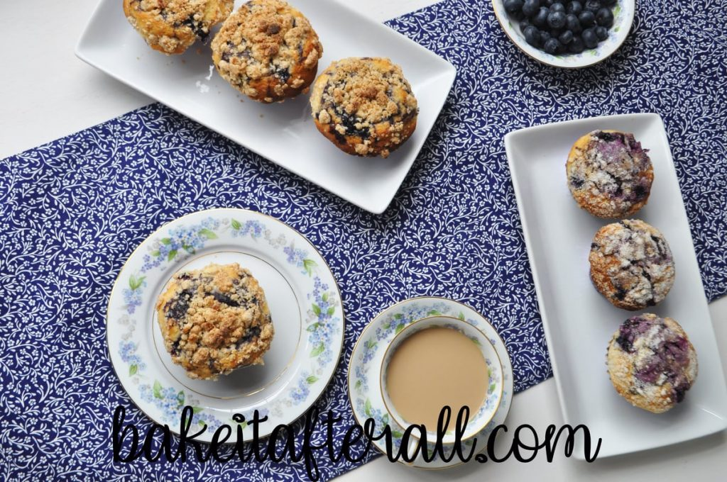overhead shot of best blueberry muffins on white platters with a blue and white flowered table runner and a cup of coffee