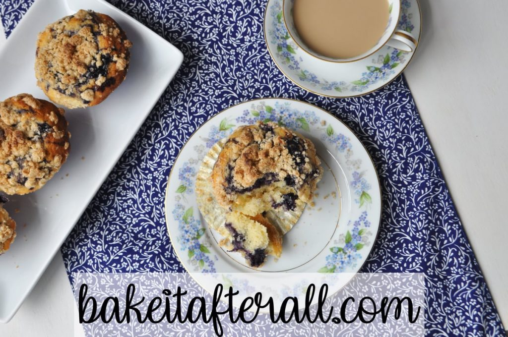 overhead shot of broken open muffin with a platter of best blueberry muffins next to it and a cup of coffee