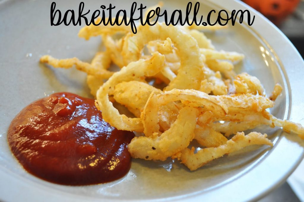 onion strings on a plate with ketchup