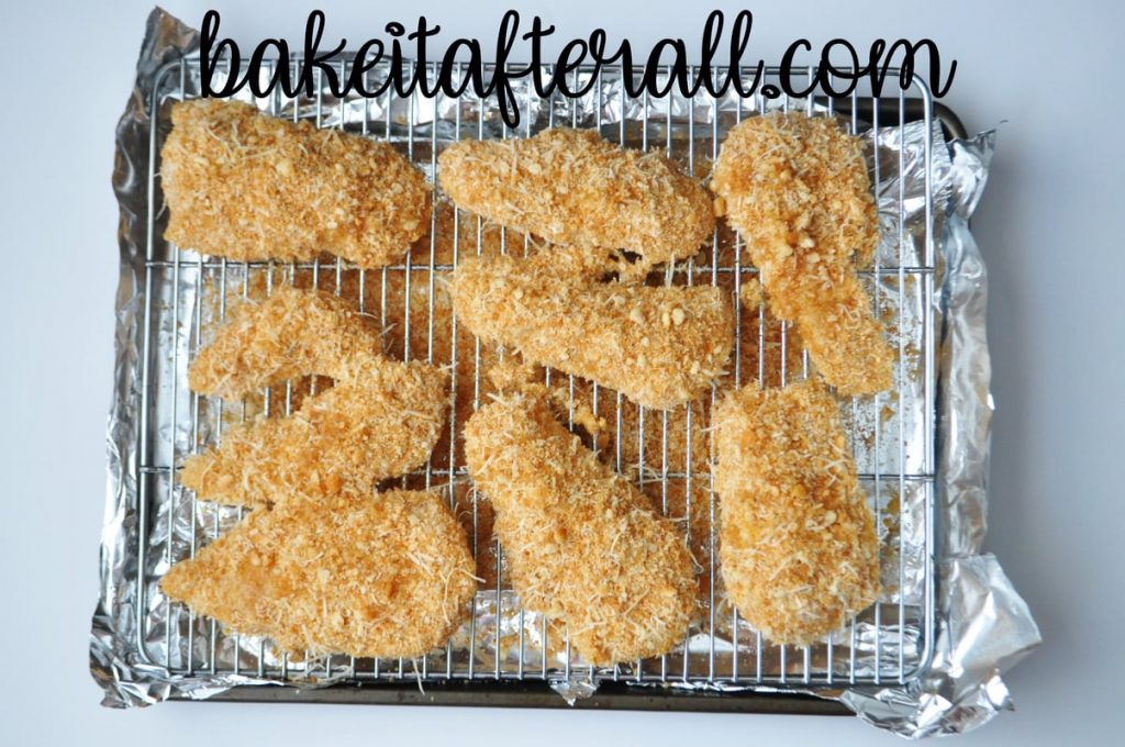 chicken parmesan pieces before baking set on a wire baking rack over a baking sheet