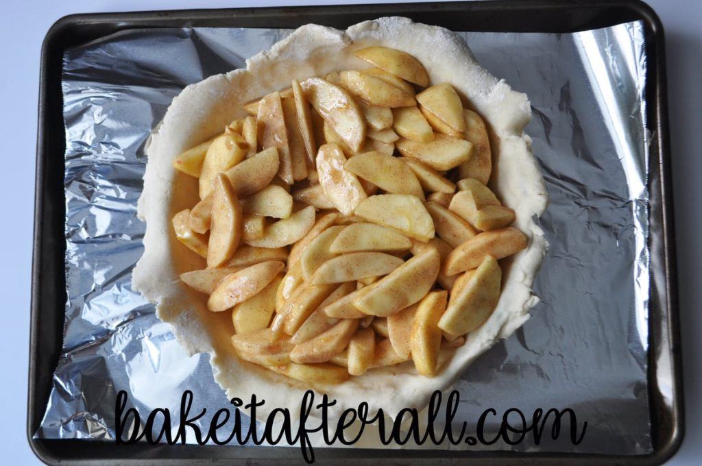 apple filling inside a pie plate lined with pie crust on an aluminum lined baking sheet