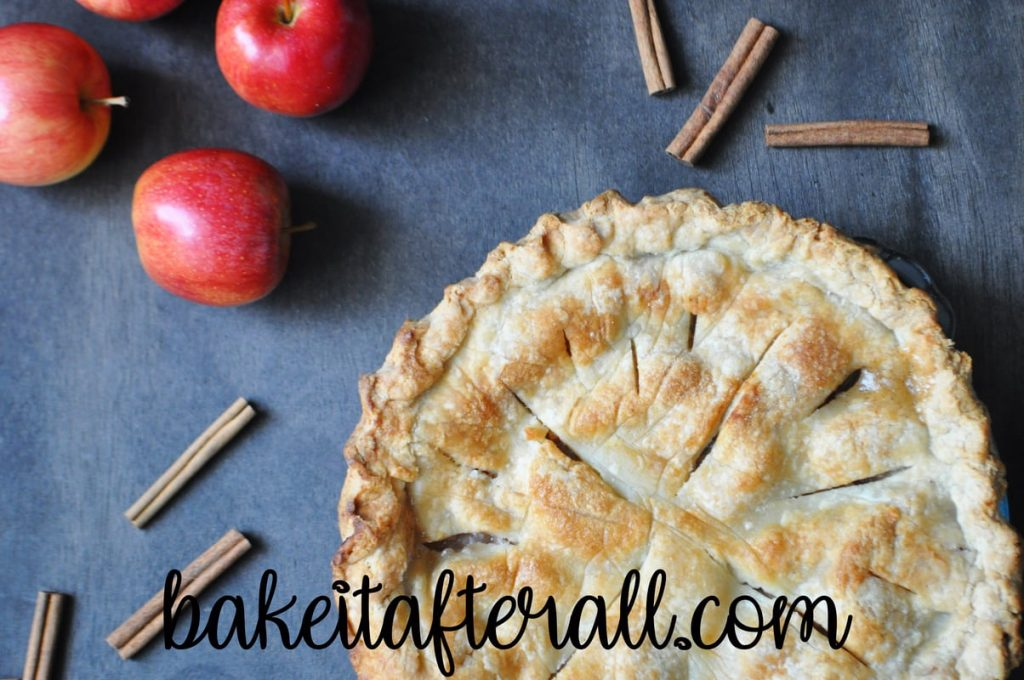 classic apple pie on a wood table with cinnamon sticks and apples