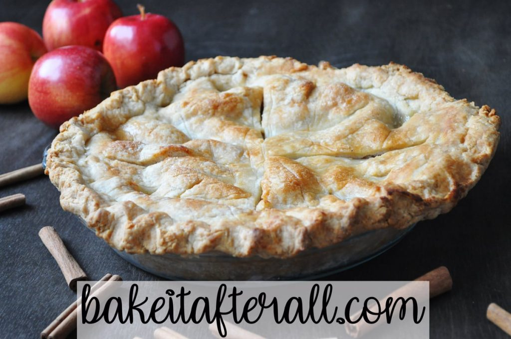 classic apple pie on a wood table with apples and cinnamon sticks