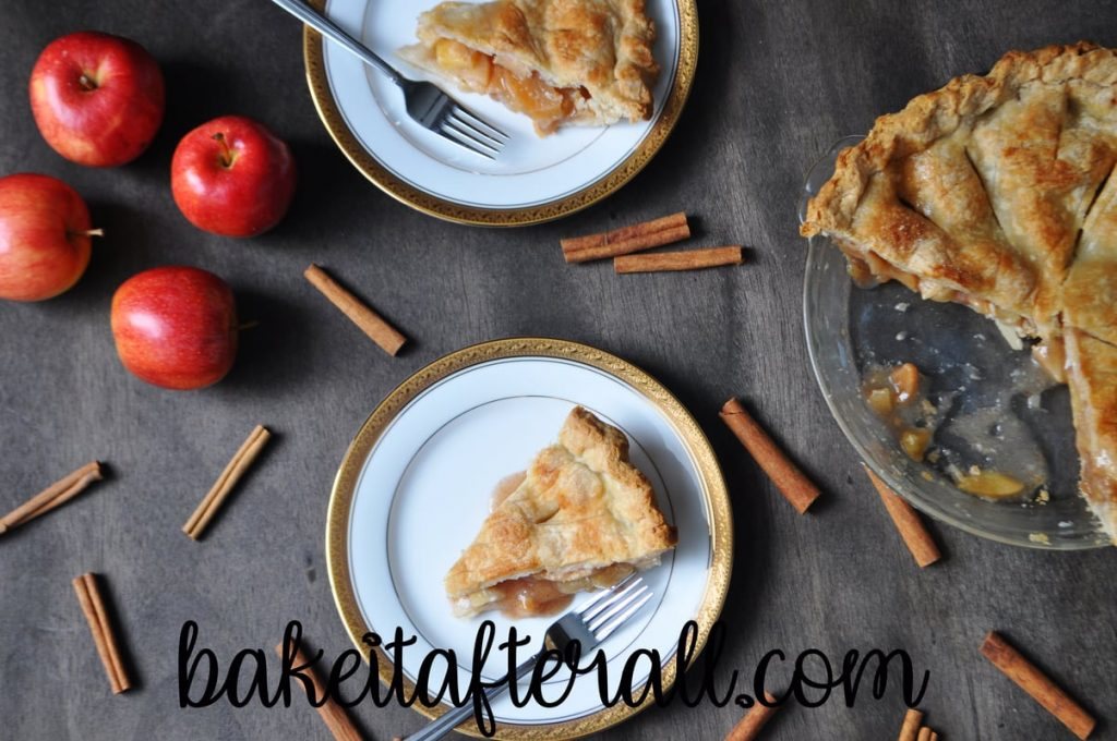 classic apple pie on a plate with a cut into pie plate and apples and cinnamon sticks
