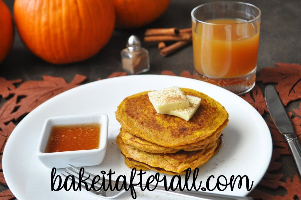 pumpkin pancakes on a white plate with syrup and a glass of apple cider