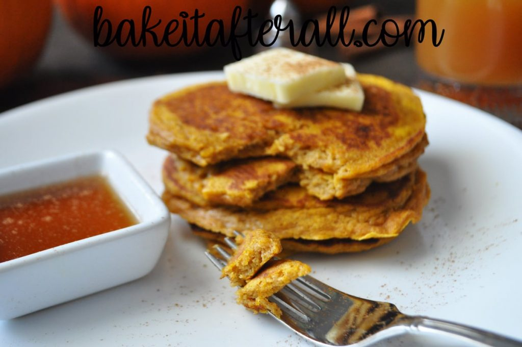 pumpkin pancakes on a white plate with a fork