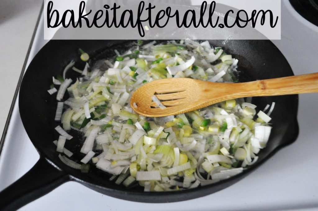 leeks and jalapenos sauteeing in butter in a cast iron skillet