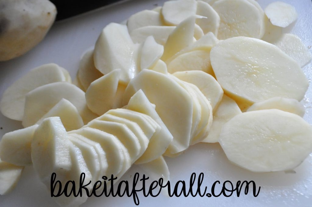 peeled and thinly sliced potatoes on a cutting board