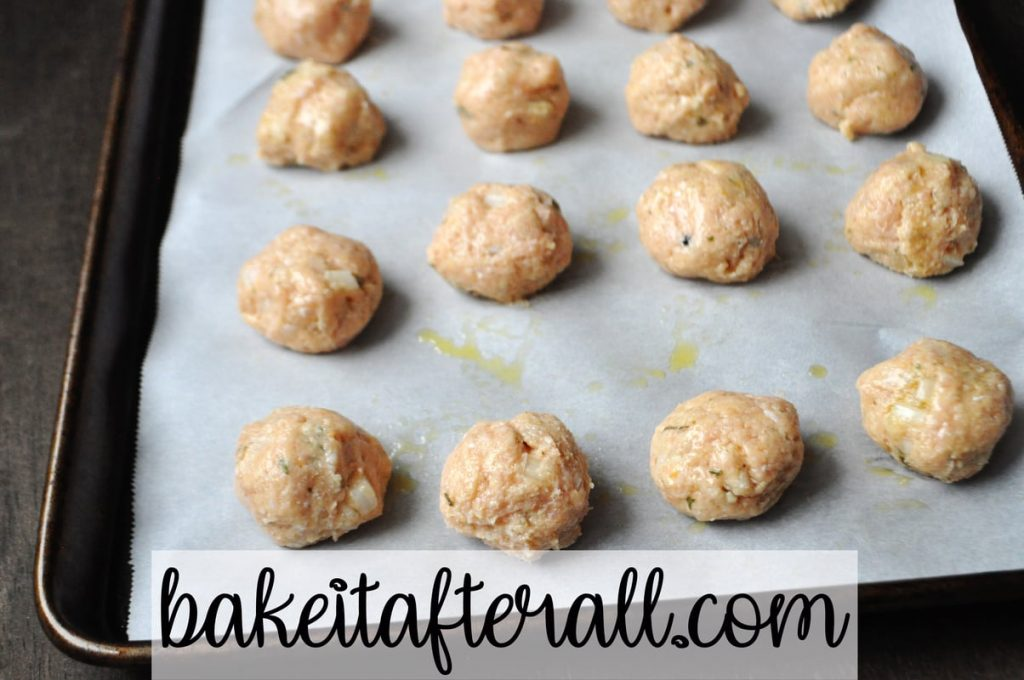 uncooked chicken meatballs on a baking sheet
